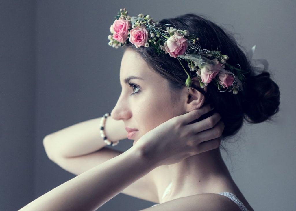 Braut und rosefarbener Blumenkranz in Szene gesetzt
