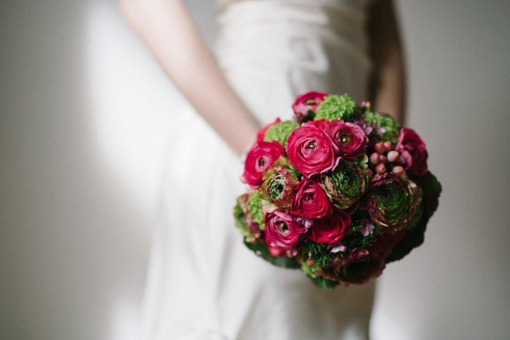 Kugelförmiger Brautstrauß mit kräftigen Rosen in knalligem Magenta.