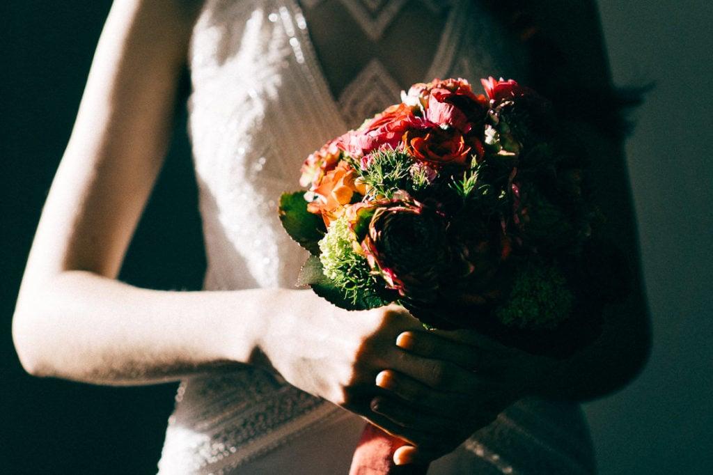 Detailsaufnahme des magentafarbenen Brautstraußes während des Brautshootings in Berlin