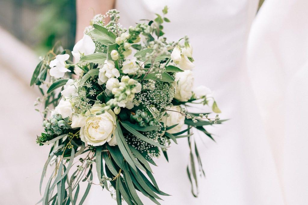 Der Brautstrauß mit silbergrauem Grün und weißen Blumen, locker gebunden. Hochzeitsfotografie.