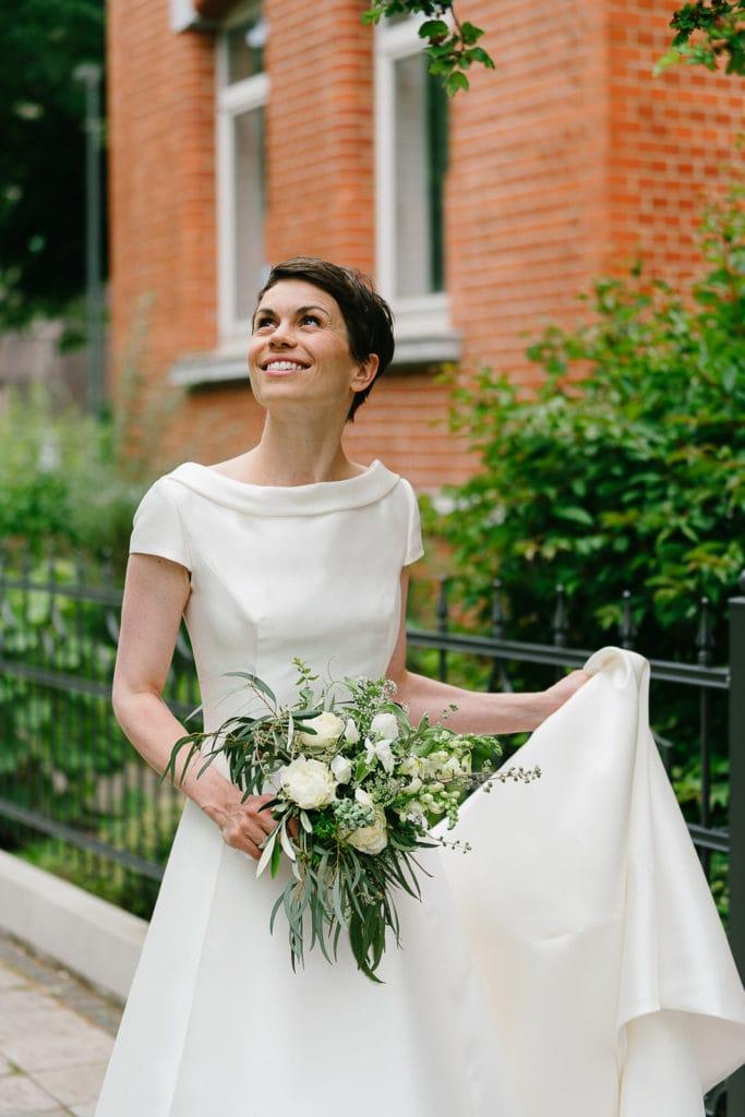 Die Braut auf dem Weg zum Paarshooting mit Brautstrauß und Schleppe in der Hand. Hochzeitsfotografie.
