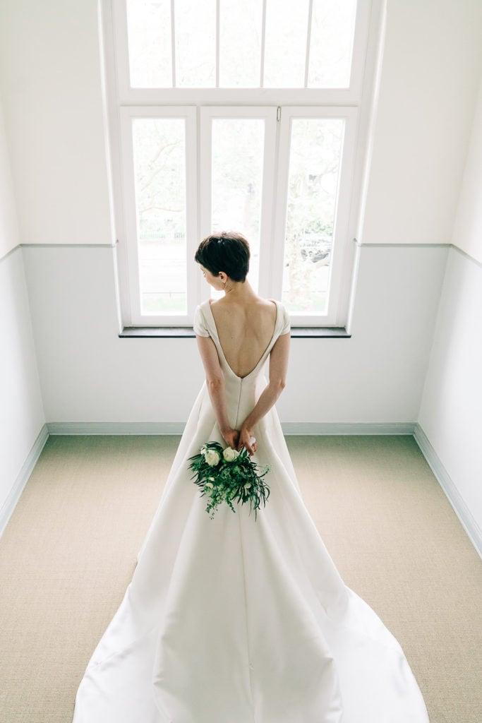 Das traumhafte Brautkleid und die wunderschöne Braut vor einem hellen Fenster in Szene gesetzt. Hochzeitsfotografie. Brautshooting.
