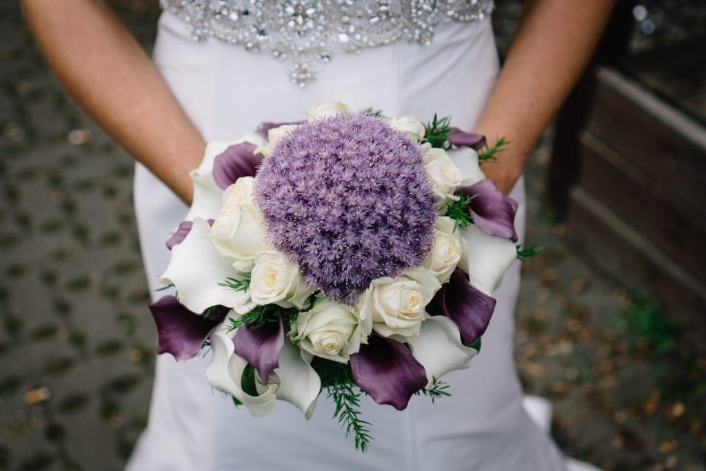 Kugelförmiger Brautstrauß mit Allium als zentrale Blüte und Blickfänger. Der lavendelfarbene und weiße Strauß überzeugt durch seine Einzigartigkeit.