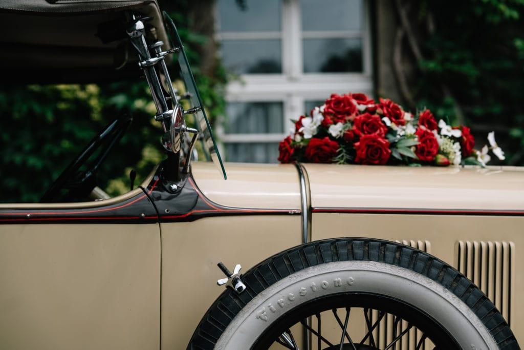 Brautschmuck in Rot auf einem Oldtimer als Hochzeitsgefährt.