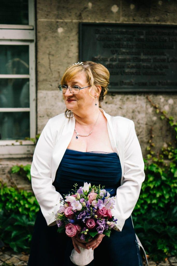 Die wartende Braut mit ihrem Brautstrauß vor der Trauung im Rathaus Spandau.