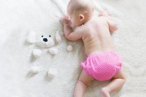 Klassisches Babyfoto im ersten Jahr: Baby auf seiner Spieldecke mit Spielzeug
