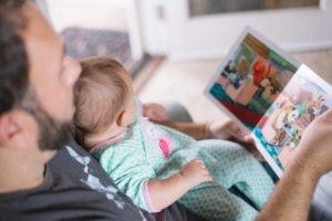 Klassisches Babyfoto: Vater liest seinem Kind vor.