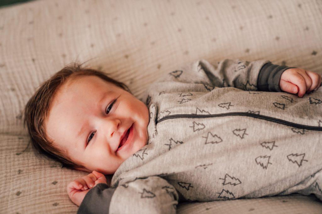 Ein klassisches Babymotiv im ersten Babyjahr: Lächelndes Kind auf dem Rücken liegend.