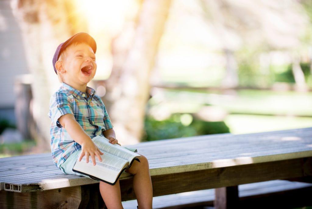 Kind auf der Bank beim Lachen