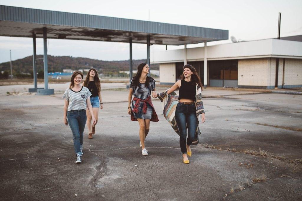 Vier Mädels rennen an einem bewölkten Tag auf die Kamera zu.