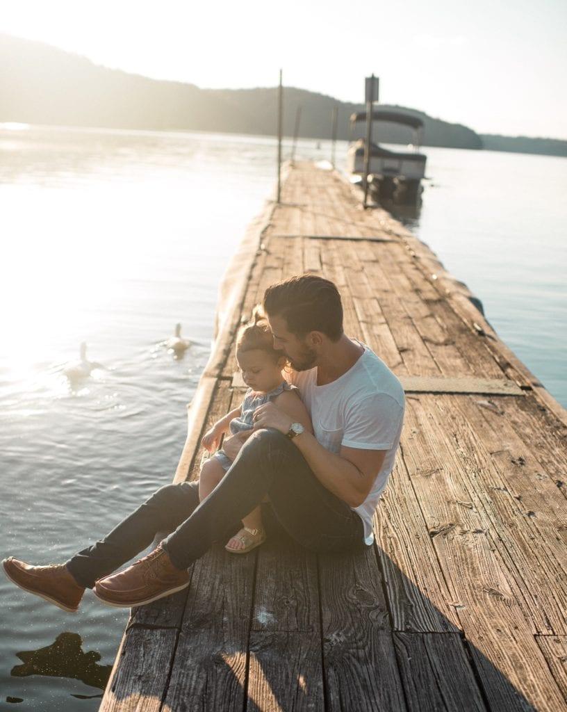 Mann sitzt mit Kind am Pier