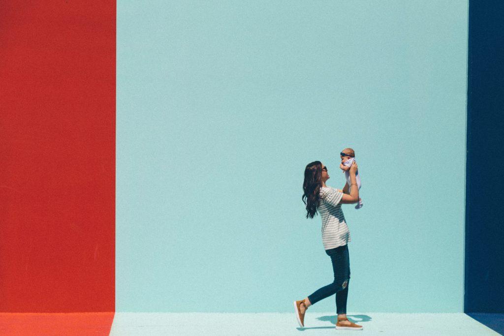 Fotografie einer Mutter vor einem farbigen Hintergrund mit Baby