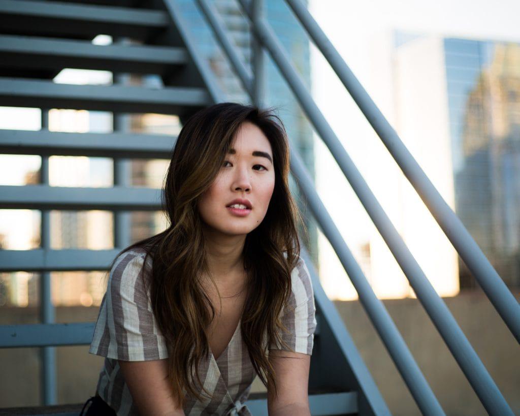 Junge Frau sitzt im Schatten auf einer Treppe.