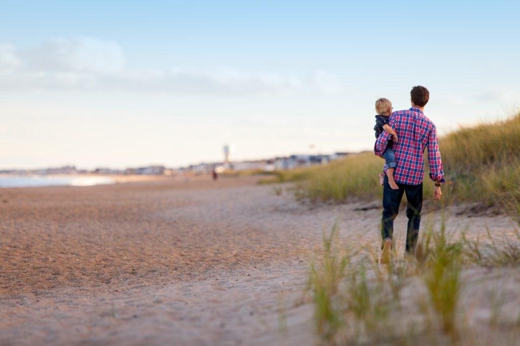 Cater am Strand mit seinem Kind im Arm