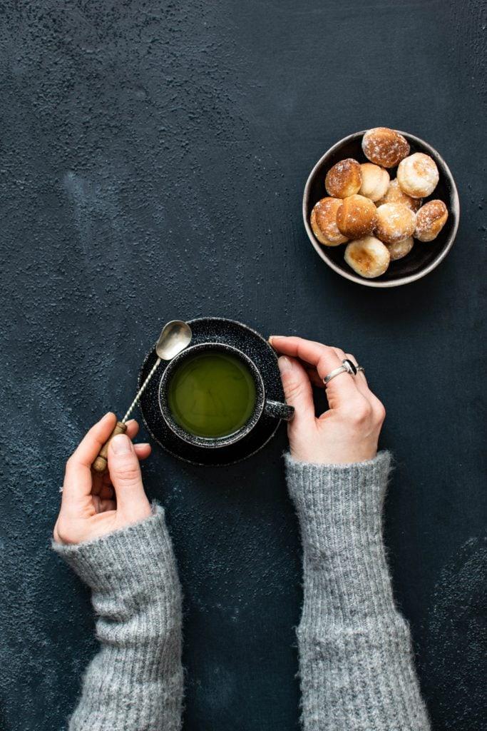 Top-Down-Bild mit den Händen einer Frau und Tee.
