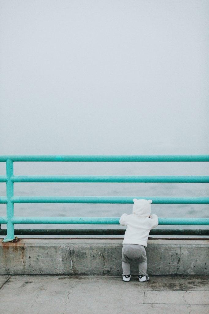 Kleinkind steht an der Pier