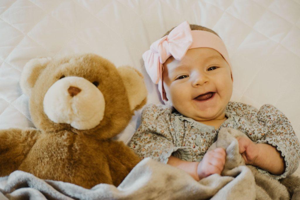 Lachendes Baby nebem einem riesigen Teddybären
