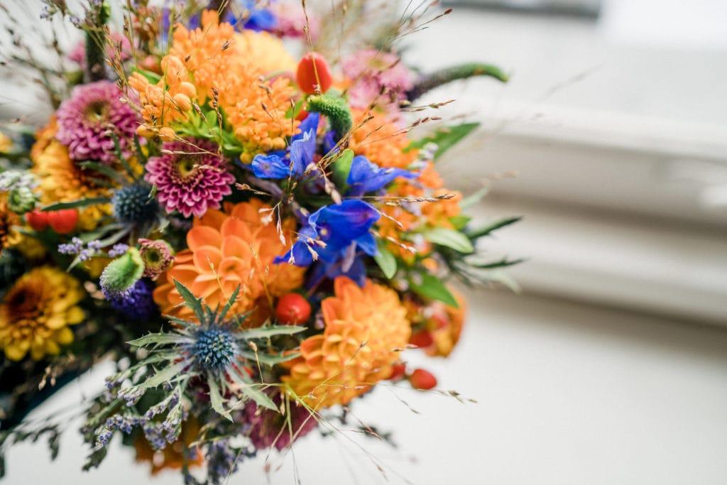 Hochzeitsstrauß mit orangenen Dahlien, violetten Disteln und dunkelrosanen Margarithen auf einer Fensterbank.