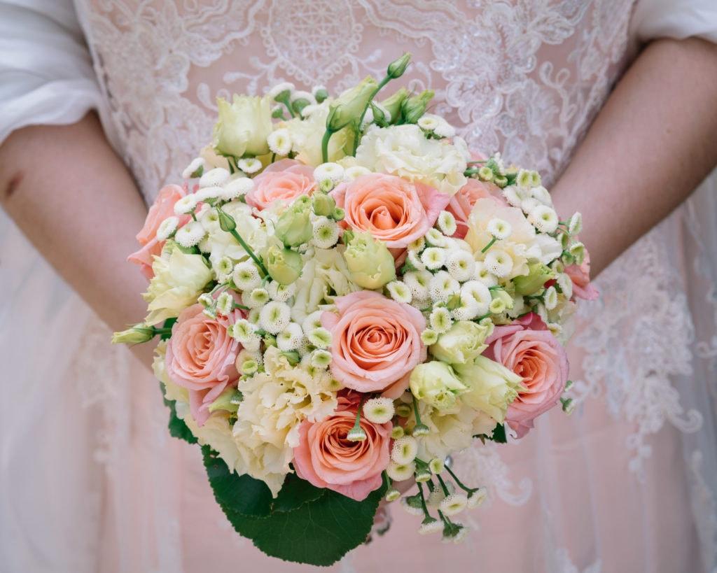 Brautstrauß perfekt abgestimmt zum leicht koralle-farbenen Hochzeitskleid.