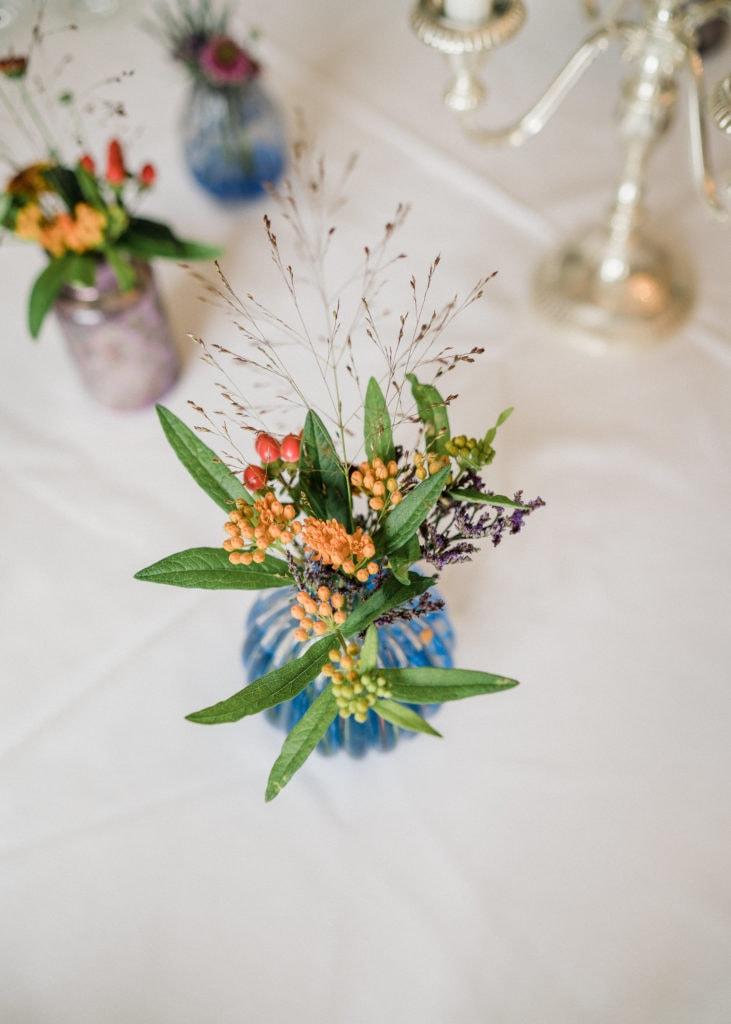 Gräser und Blumen mit kleinen Knospen in violett und orange als Hochzeitsfloristik.