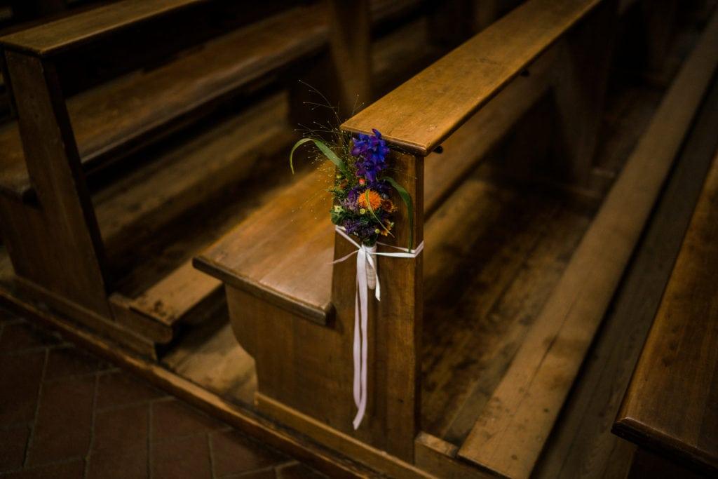 Dekoration einer Kirchenbank mit orangenen und violetten kleinen Blumensträußen.