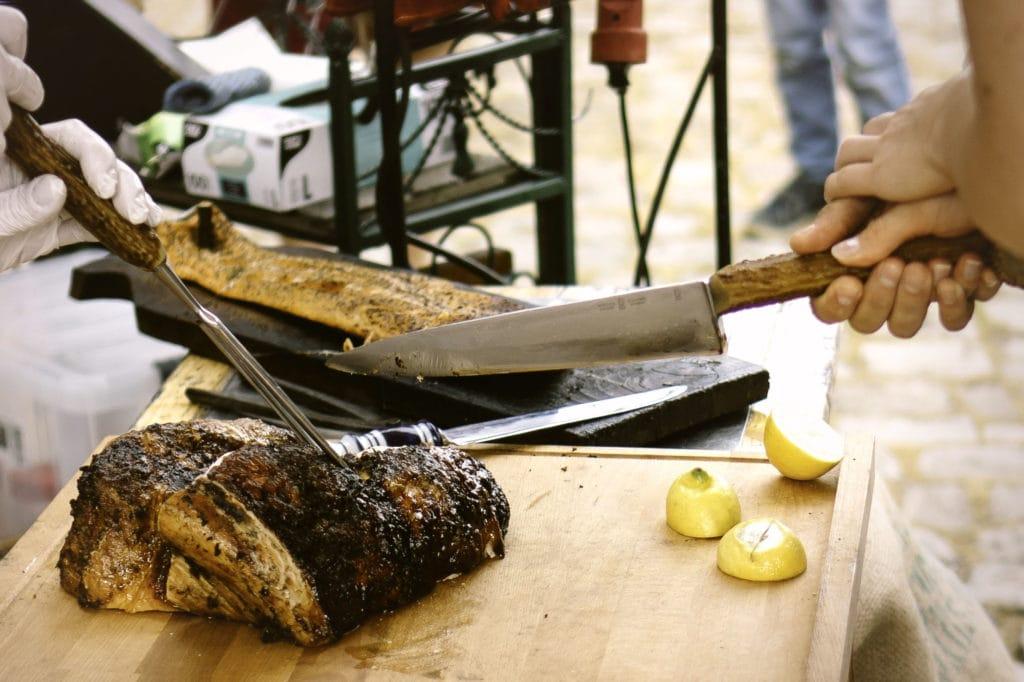Anstelle einer Hochzeitstorte wird ein Stück Fleisch vom Grill gemeinsam angeschnitten.